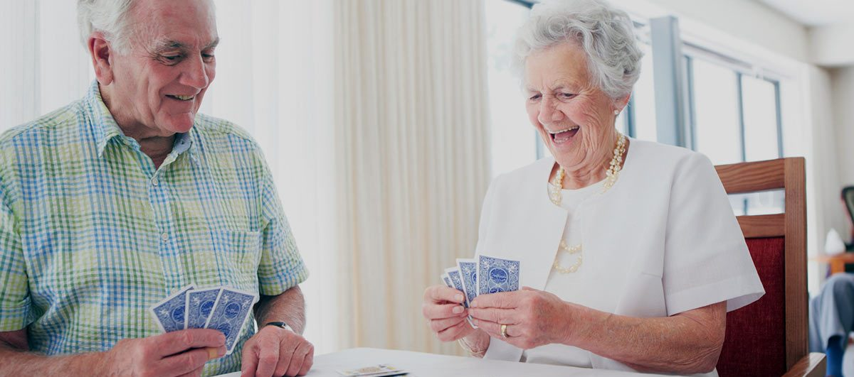 older couple playing cards secured in home by Amherst Alarm